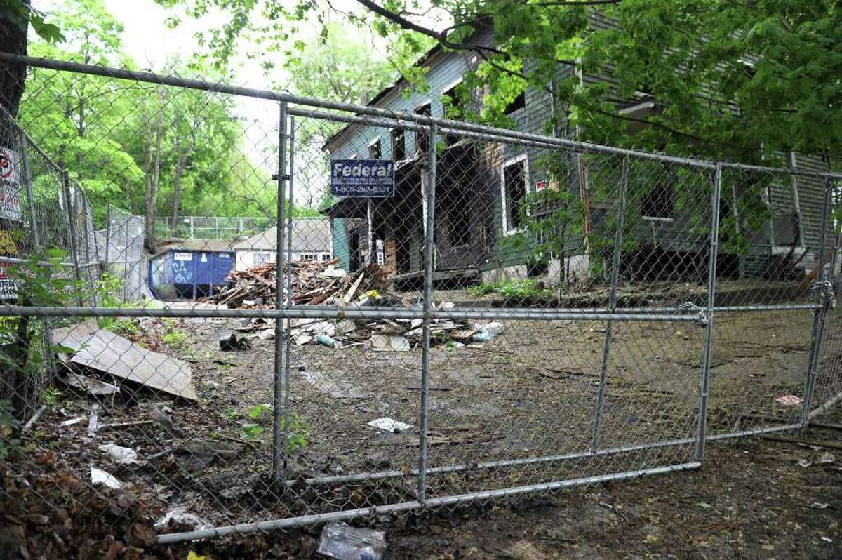 Behind the fence is a large pile of construction debris that was dumped recently at a blighted property near Rose Street. The owner is planning to develop low income rental housing on the site and is offering a reward for any information leading to the identity of the person responsible for the dumping.