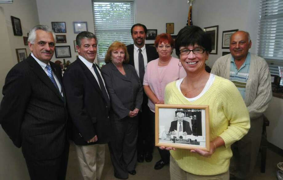 Nora Dwyer holds a photograph of her father Jack Dwyer, who died of cancer in 2001, while announcing this year's 10th Annual Tribute to Jack Dwyer, along with (left to right) Rensselaer County Clerk Frank Merola, County Legislator Lou Desso, Troy Record Editor Lisa Robert Lewis, attorney Greg Cholakis, Susan Dwyer (Jack's daughter) and Nick Nicholas, a long time friend of Jack's, in Merola's office on Monday May 16, 2011 in Troy, NY.  Lisa Robert Lewis will be honored at the dinner, which will be held June 2, 2011 at the American Legion hall in Wynantskill.  ( Philip Kamrass / Times Union) Photo: Philip Kamrass