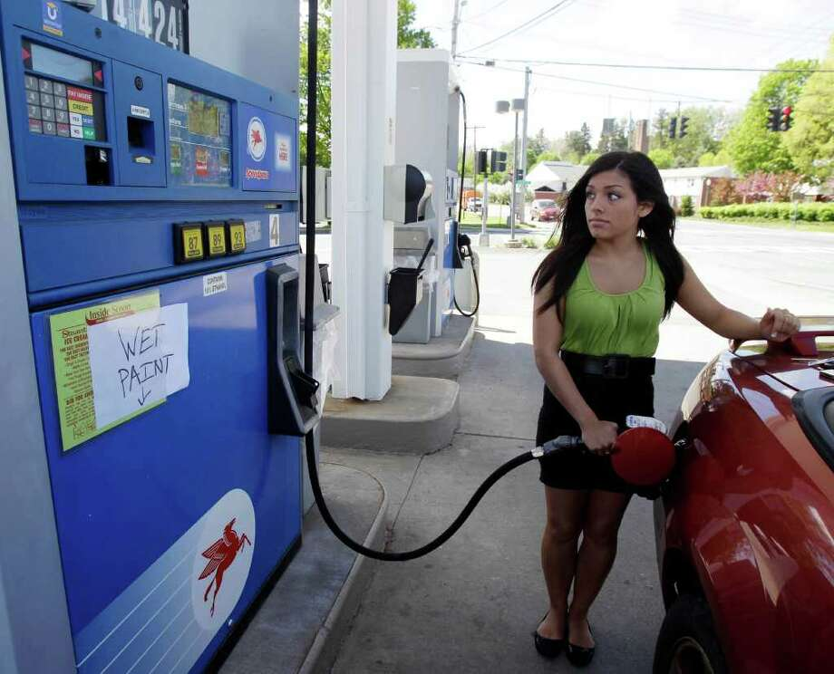 Emily Corbett of Mechanicville, N.Y., pump gas at a station in Mechanicville, on Wednesday, May 11, 2011. New York, Indiana, Illinois and New Hampshire are among the first states talking about temporarily suspending part or all of the state and local taxes that can add 14 cents to nearly 50 cents to a gallon of gas. (AP Photo/Mike Groll) Photo: Mike Groll