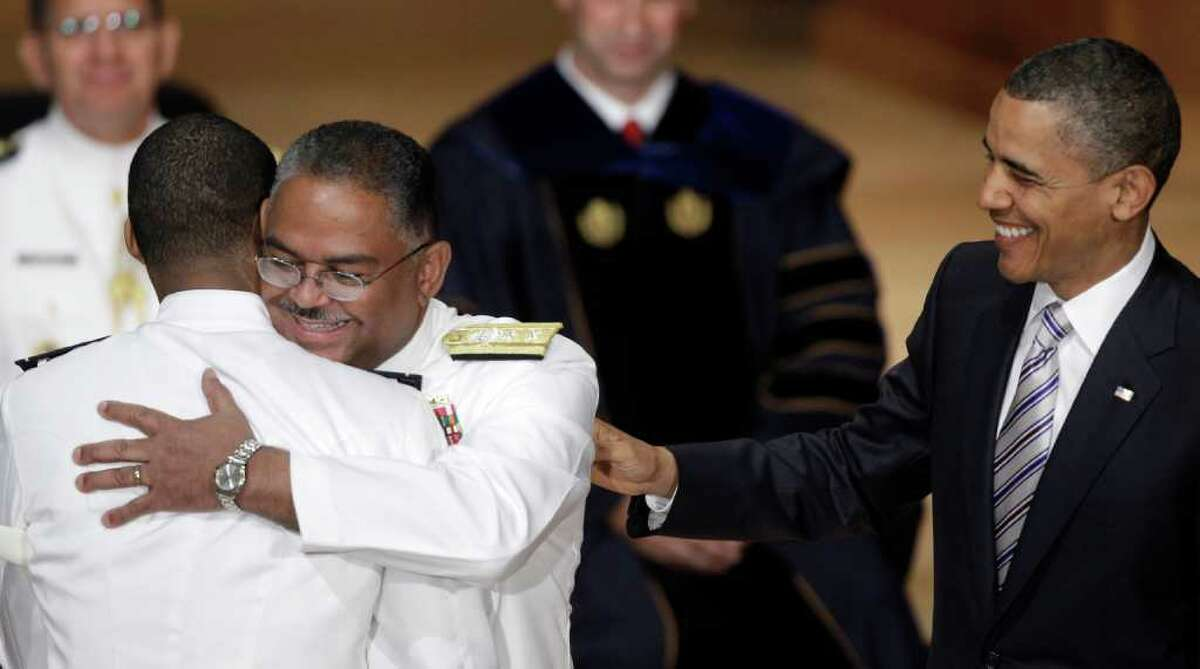 President Barack Obama looks on as newly commissioned Ensign Patrick George Bennett III receives a hug from his grandfather retired Coast Guard Rear Adm. Stephen Rochon at the 130th Coast Guard Academy graduation in New London, Conn., Wednesday, May 18, 2011. Rochon is currently serving as a White House usher. (AP Photo/Stephan Savoia)
