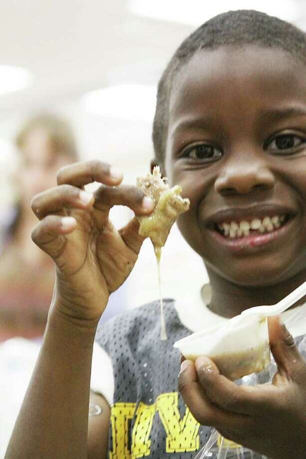 At the Taste of Leon Valley, Desmond Gant, 6, savors a piece of smothered pork steak from Janie's Soul Food, owned by Janie Gant, Desmond's grandmother. Photo: Photo By Lauri Gray Eaton