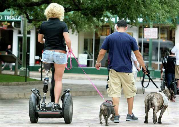Corporal Kendra Coleman walks her dog Athyna with boyfriend Anthony Garza walking Smokey back to their hotel as Segs4Vets presents mobility devices to severely wounded troops at ceremony at the front of the Alamo  on May 18, 2011.    Tom Reel/Staff Photo: TOM REEL, SAN ANTONIO EXPRESS-NEWS / treel@express-news.net