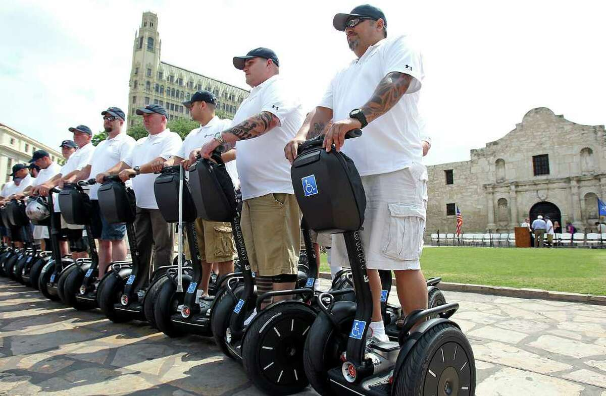 Wounded veterans line up for a group photo as Segs4Vets presents mobility devices to severely wounded troops at ceremony at the front of the Alamo on May 18, 2011.