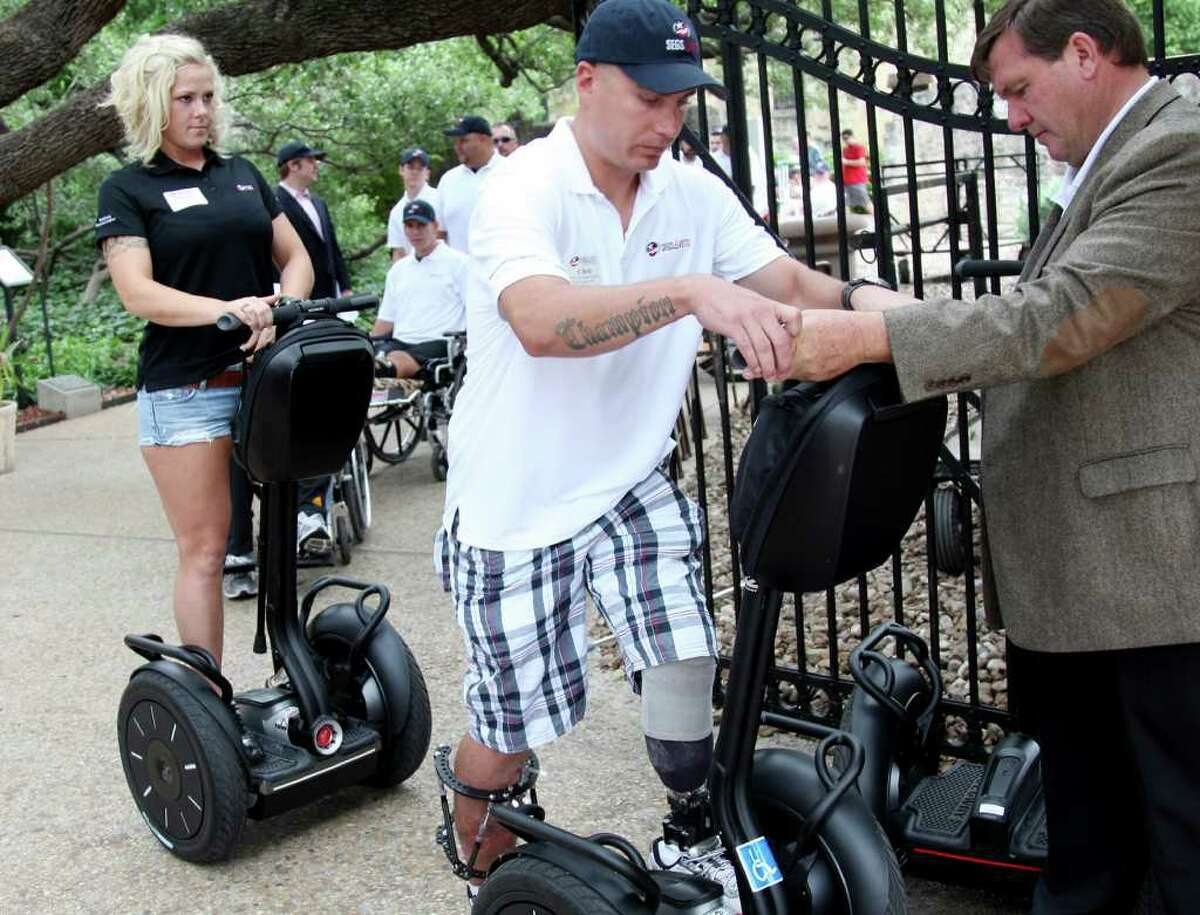 Sergeant Christopher Champion steps onto a Segway at the Segs4Vets ceremony May 18, 2011, at the Alamo.