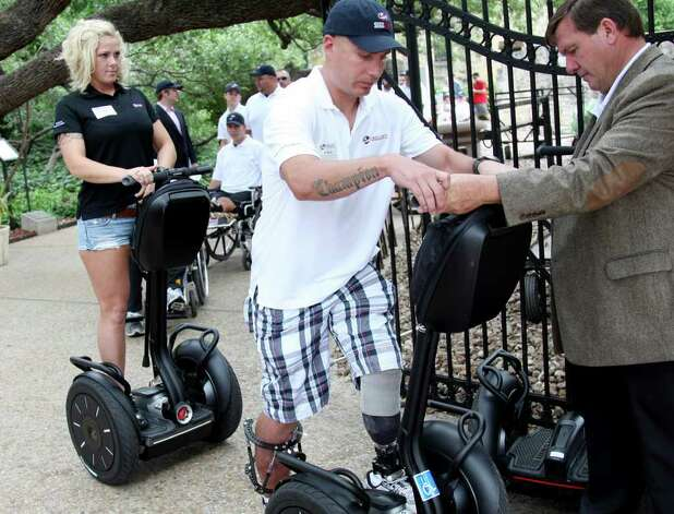 Sergeant Christopher Champion steps onto a Segway at the Segs4Vets ceremony May 18, 2011, at the Alamo. Photo: ANDREW BUCKLEY, SAN ANTONIO EXPRESS-NEWS / abuckley@express-news.net