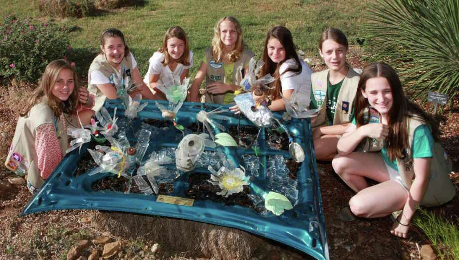 Girl Scout Silver Award-winners from Troop 1222 show off part of their community service project, an art collage crafted with trash found at Mitchell Lake. From left are Jane Emma Barnett, Katie White, Hannah Shaeffer, Addison Nelson, Hannah Ortega, Camilla Kampmann and Sarah Berton. Photo: Photo By Mary Candee
