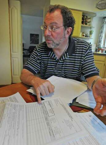 Mark Rappaport points at a figure in his truth-in-lending disclosure statement for the refinancing of his mortgage of his townhouse in Albany, N.Y. on Wednesday May 4, 2011. (Lori Van Buren / Times Union) Photo: Lori Van Buren
