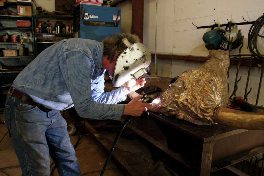 Larry Stevens, owner of Stevens'Foundry in Bulverde, welds a horn to the head of one of the longhorns that will be part of the massive Tejano monument being installed on the state capitol grounds next spring. Photo: Photo Courtesy Of IBC Bank
