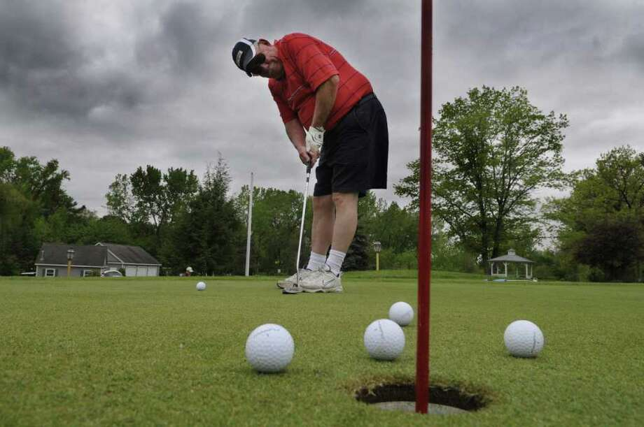 Lanny Livingston of Latham gets out between rain showers to work on his short putting game on the practice green at Mill Road Acres Golf Course and Mill Road Restaurant on Wednesday afternoon, May 18, 2011 in Latham.  The public course is an 18-hole par 3 course and it also has a driving range.  (Paul Buckowski / Times Union) Photo: Paul Buckowski