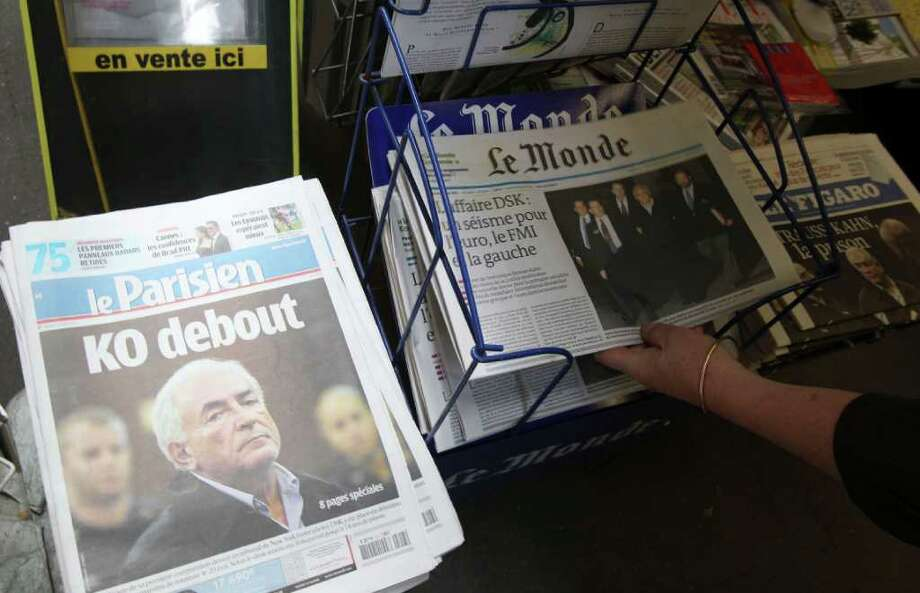 A woman picks up a copy of a newspaper headlining on IMF head arrest at a news stand in Paris, Tuesday May, 17, 2011. International Monetary Fund chief Dominique Strauss-Kahn was accused Monday of a pattern of sexual misconduct that began years before he was charged with a weekend attack on a maid in a New York hotel room. Headline of Le Parisien reqds: standing KO. (AP Photo/Michel Euler) Photo: Michel Euler / AP