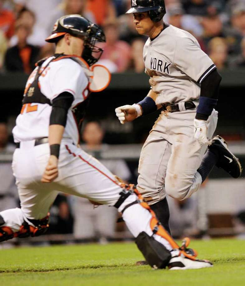 New York Yankees' Alex Rodriguez, right, comes in to score against Baltimore Orioles catcher Matt Wieters, left, on a sacrifice fly by Yankees' Nick Swisher during the fourth inning of a baseball game on Wednesday, May 18, 2011, in Baltimore. (AP Photo/Nick Wass) Photo: Nick Wass