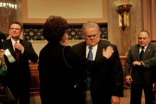 Diana Hagee brushes off the coat worn by her husband, San Antonio Pastor John Hagee, center, as he waits for Texas Senators John Cornyn and Kay Bailey Hutchison to arrive for a private meeting with the Christians United for Israel Texas delegates in the Dirksin Building at the United States Capitol on Wednesday, July 18, 2007. At right is Paul J. Chapa, a member of Hagee's security team and a member of Cornerstone Church and at left is Pastor George Pearsons of Ft. Worth, TX.  Photo: LISA KRANTZ, SAN ANTONIO EXPRESS-NEWS / SAN ANTONIO EXPRESS-NEWS