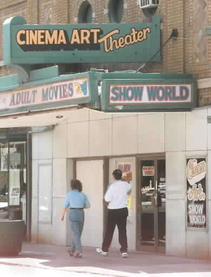 Pedestrians pass under the Cinema Art Theater marquee on River Street in Troy Friday, June 4, 1999. A plan proposed by architects for the city of Troy would convert the theater into the chambers for the City Council. (File photo)