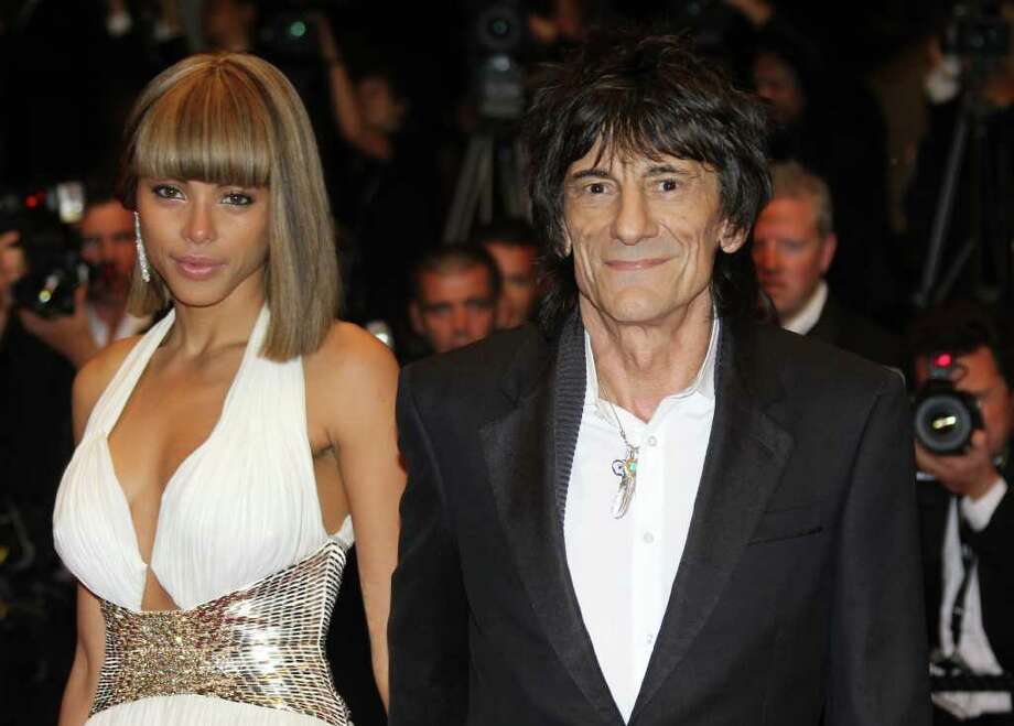 "British guitarist Ronnie Wood and Ana Araujo pose on the red carpet before the screening of ""Melancholia"" presented in competition at the 64th Cannes Film Festival in Cannes. Photo: AFP/Getty Images"