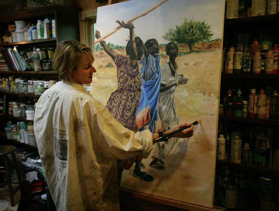 Artist Cynthia Davis works on a large canvas in her Trumbull home studio as part of her Sudan Canvas Project. Davis has recruited other Connecticut artists to create works to raise funds for the ongoing crisis in the African country Sudan. Photo: Brian A. Pounds / Connecticut Post