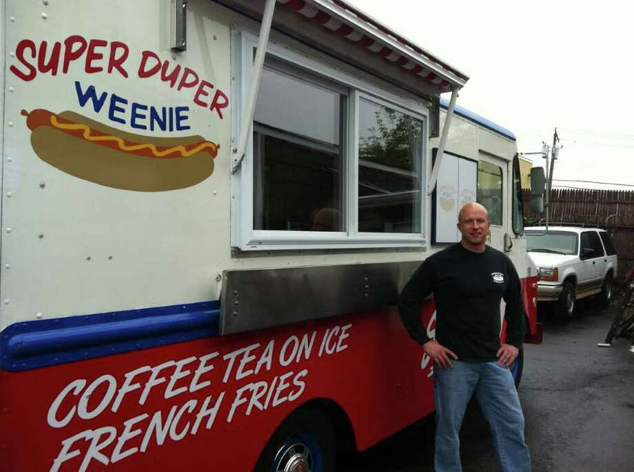 John Pelligrini, co-owner of Super Duper Weenie Hot Dogs, stands next to one of the business' four mobile catering trucks. Photo: Contributed Photo