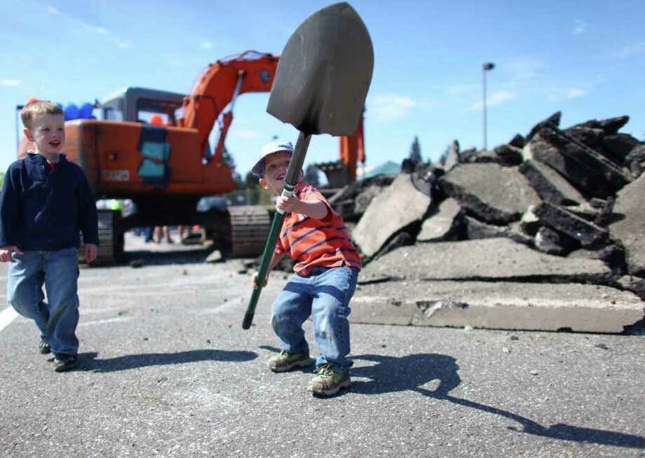 Josh Soderlund, 3, hoists a shovel used to break ground at the new Dick's Drive-In during a cermonial groundbreaking for the restaurant on Highway 99 in Edmonds. Soderlund's dad Aaron was chosen as one of the Fab Fan winners that helped turn soil during the ceremony. Photo: JOSHUA TRUJILLO / SEATTLEPI.COM