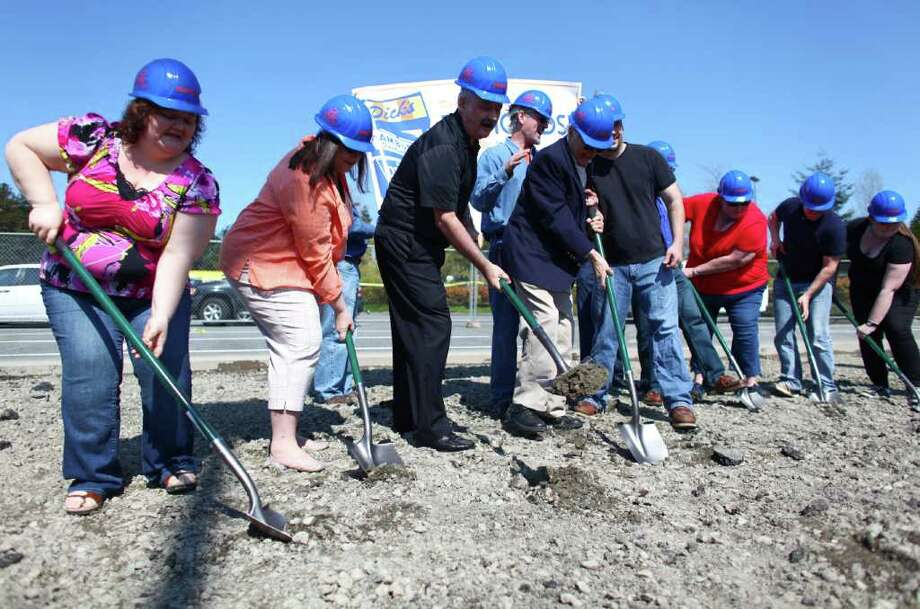 Fab Fan winners turn soil with Dick Spady, center, during the groundbreaking for the new Dick's Drive-In on Thursday, May 19, 2011 on Highway 99 in Edmonds. The fans of the restaurant had to write a story of 50 words or fewer about why they are a fan of the restaurant. Winners were chosen for the groundbreeaking. Photo: JOSHUA TRUJILLO / SEATTLEPI.COM