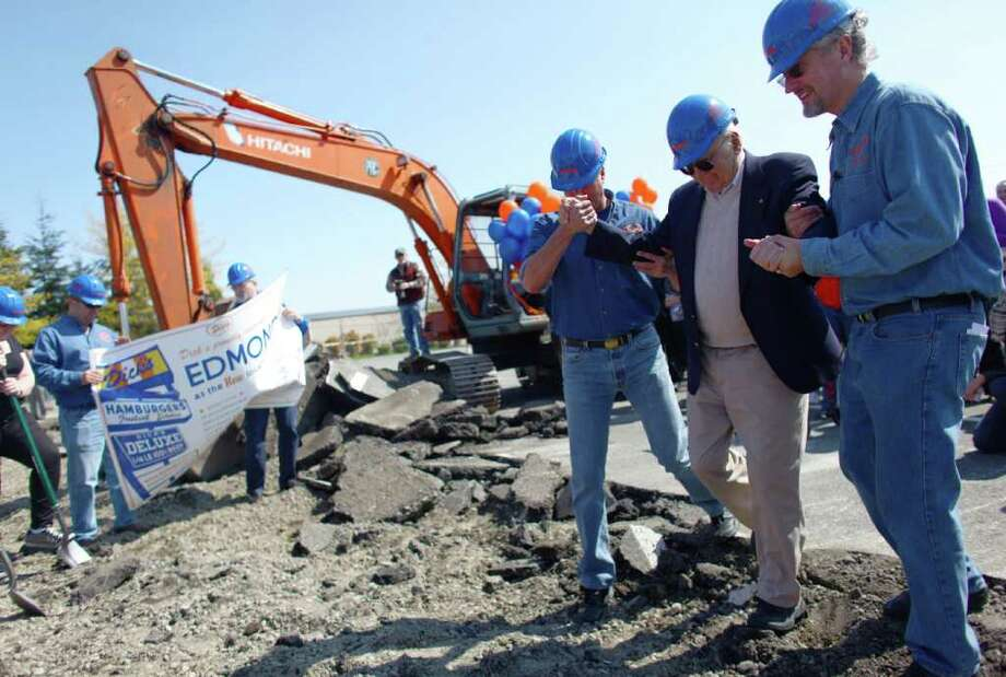 Dick Spady is helped across broken pavement during the groundbreaking for the new Dick's Drive-In on Thursday, May 19, 2011 on Highway 99 in Edmonds. Photo: JOSHUA TRUJILLO / SEATTLEPI.COM