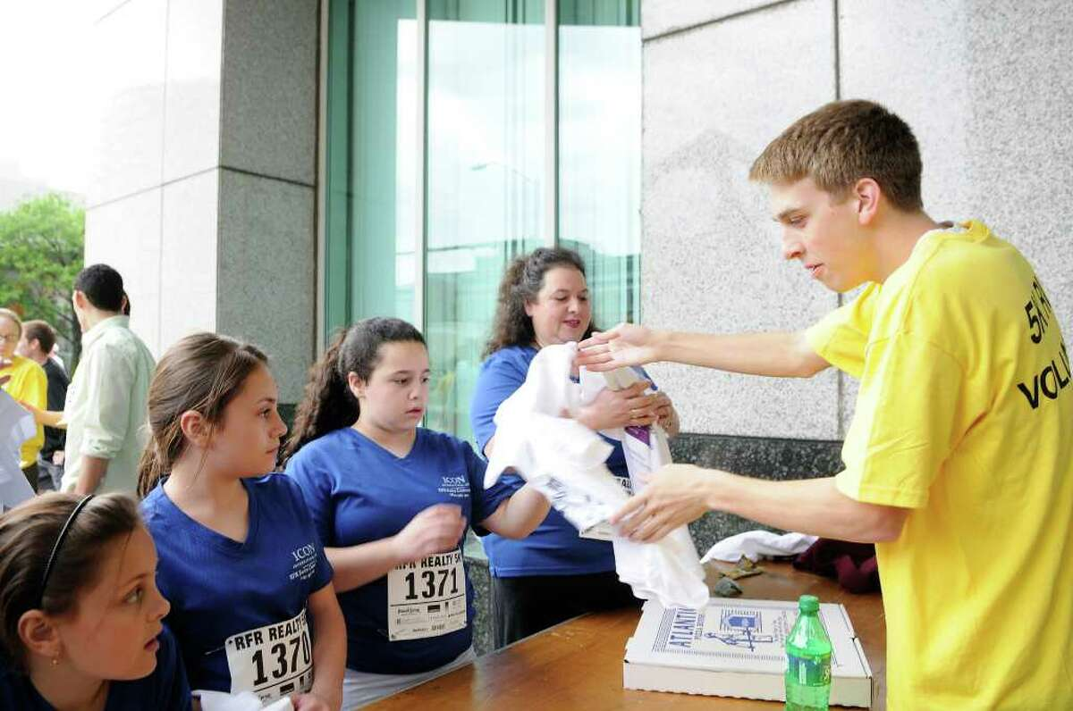 Members of Team Icon collect shirts from volunteer Robert Salandra, Fairfield. L to R: Alyssa Salamone, 9, Bronx NY, her sister Stefanie Salamone, 12, Sophia Cirigliano, 12, Bronx, NY, her mom Paula Cirigliano, who works for Icon in Stamford. More than 1,900 participants gathered for the RFR Realty Corporate 5K Run/Walk in downtown Stamford, CT on Thursday, May 19, 2011 for a fundraiser to benefit the Boys & Girls Club of Stamford.