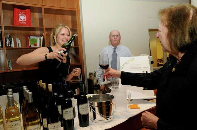 Camey Brown, Norwalk, pours wine for Christine Irvin, Stamford, as guests gather at the Ferguson Library in Stamford, CT on Thursday, May 19, 2011 for a fundraiser to benefit the library. Irvin is head of the Stamford Art Association, which coordinates art exhibits on the library's second floor. Photo: Shelley Cryan / Shelley Cryan freelance; Stamford Advocate freelance
