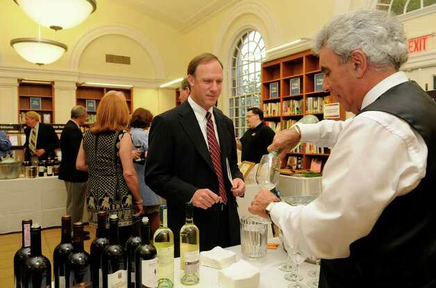 Ralph Iera, Stamford, pours wine for Tom Gawlak, Shelton, as guests gather at the Ferguson Library in Stamford, CT on Thursday, May 19, 2011 for a fundraiser to benefit the library. Photo: Shelley Cryan / Shelley Cryan freelance; Stamford Advocate freelance