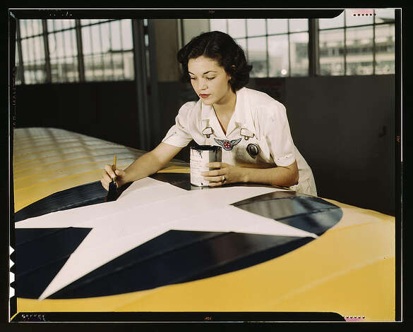 Mrs. Irma Lee McElroy painting the American insignia on airplane wings, Naval Air Base, Corpus Christi, Texas. Aug. 1942. Photo: Library Of Congress 1940s Color Photo Collection / No known restrictions on publication