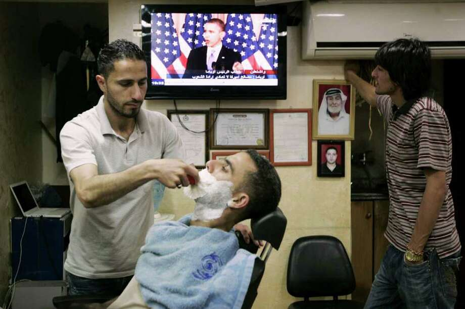 "A Palestinian barber shaves a customer during a speech by U.S. President Barack Obama, in the West Bank city of Ramallah, Thursday, May 19, 2011. Trying to advance debate in the explosive Middle East, President Barack Obama on Thursday endorsed a key Palestinian demand for the borders of its future state and prodded Israel to accept that it can never have a truly peaceful nation that is based on ""permanent occupation."" Obama's urging that a Palestinian state be based on 1967 borders - those that existed before the Six Day War in which Israel occupied East Jerusalem, the West Bank and Gaza - was a significant shift in U.S. policy and seemed certain to anger Israel. (AP Photo/Majdi Mohammed) Photo: Majdi Mohammed / AP"