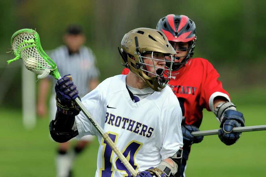 CBA's John Bassett (14), left, carries the ball as Schenectady's Joe Moore (24) defends during their lacrosse game on Thursday, May 19, 2011, at Christian Brothers Academy in Colonie, N.Y. (Cindy Schultz / Times Union) Photo: Cindy Schultz