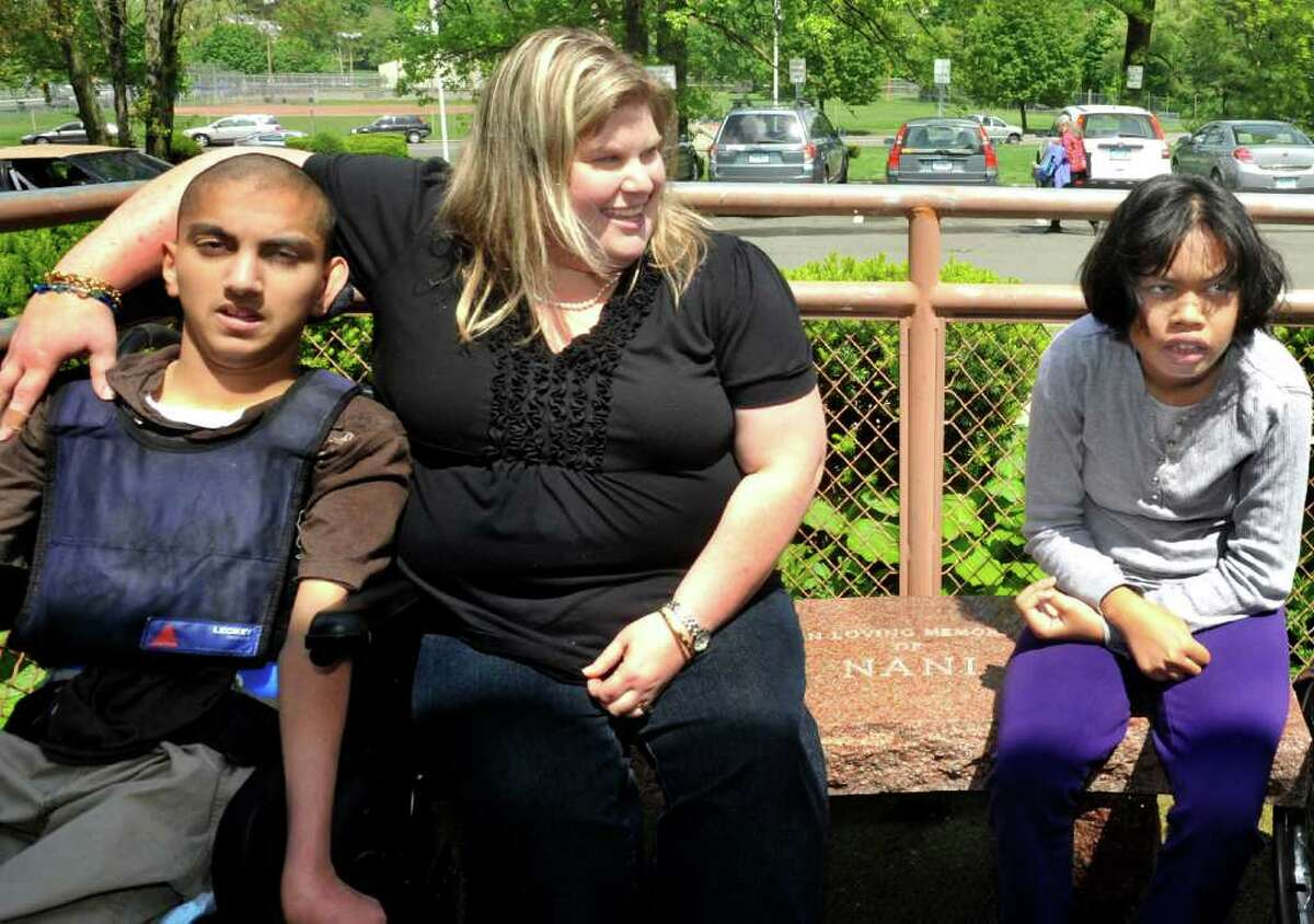 Micjohn Kainathara, 16, left, special education teacher Marlene Frank, and Lillian Touch, 16, right, sit on a stone bench that is a memorial to Nilcidairy