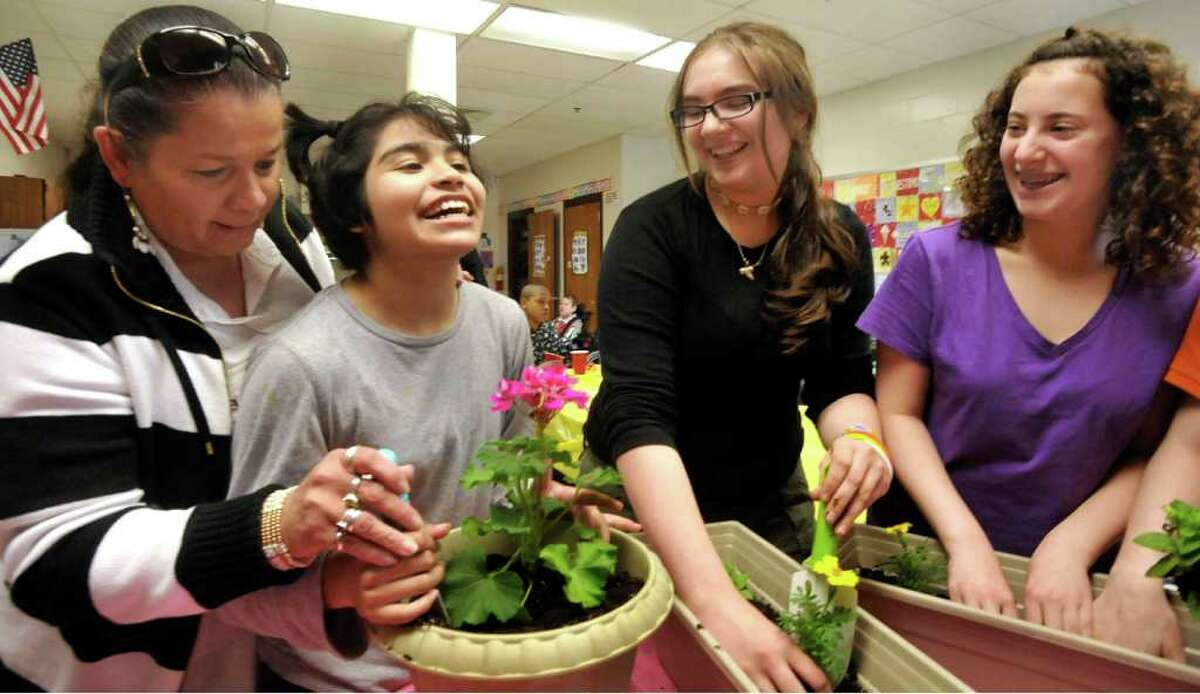 Pictured from left are Betty Gonzalez, who is helping Jenny Garcia, 16, along with Larisa Chetcuti and Emma Finkelstein, both 14, fill planters to place at a stone bench that is a memorial to Nilcidairy
