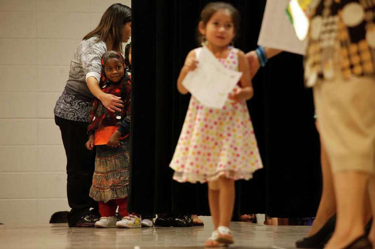 metro - Shamso Hassan, 5, left, originally from Somalia, waits her turn to walk across the stage and get her certificate while Abbygail Besa, 5, right, gets hers during the graduation ceremony for Culebra Head Start students including many refugee students at The Neighborhood Place in San Antonio on Friday, May 20, 2011. LISA KRANTZ/lkrantz@express-news.net