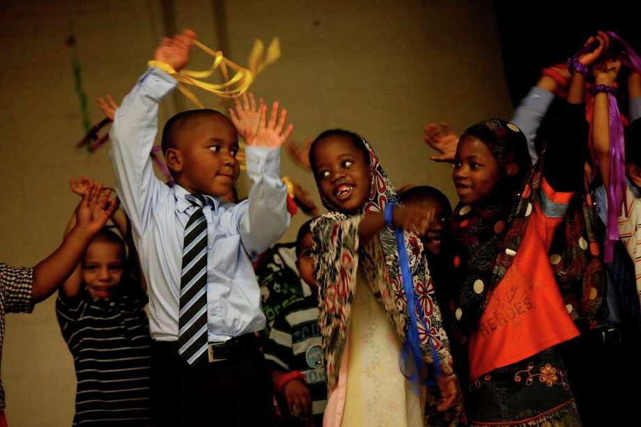 "Daron Johnson (tie), 5, (from left), Subriya Ali, 5, and Shamso Hassan, 5, sing ""Hello"" for their guests during the graduation ceremony for Culebra Head Start students including many refugees at The Neighborhood Place in San Antonio. Ali and Hassan are originally from Somalia. Photo: LISA KRANTZ, Lisa Krantz/Express-News / SAN ANTONIO EXPRESS-NEWS"