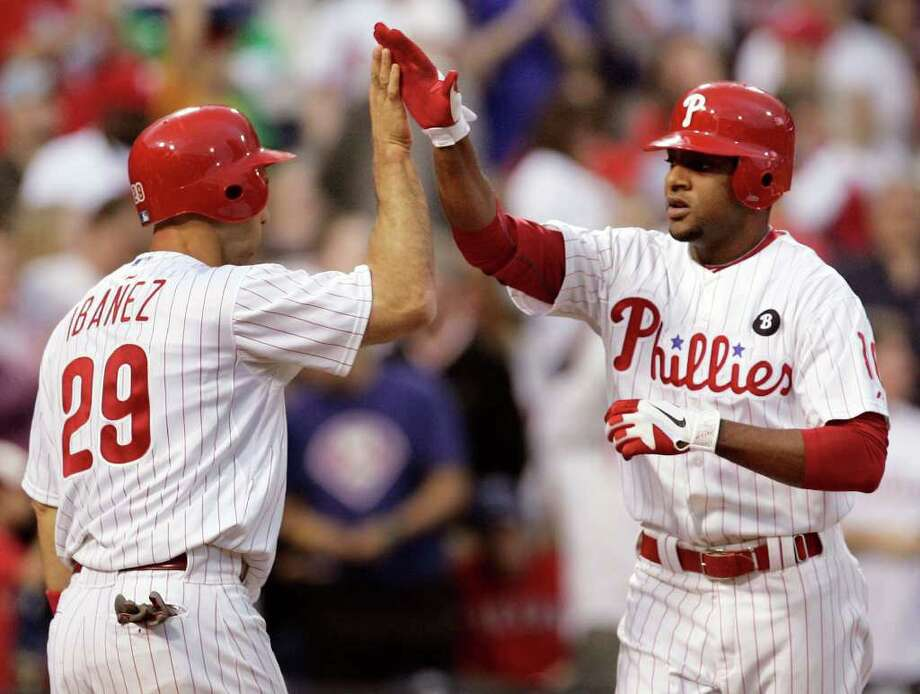CORRECTS ID OF PLAYER AT RIGHT TO BEN FRANCISCO, NOT JOHN MAYBERRY - Philadelphia Phillies' Raul Ibanez, left, hi-fives Ben Francisco, right, whose two-run home run drove in Ibanez during the second inning of an interleague baseball game with the Texas Rangers, Friday, May 20, 2011, in Philadelphia. (AP Photo/Tom Mihalek) Photo: Tom Mihalek