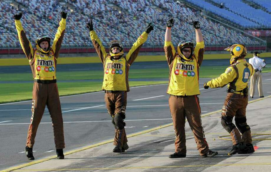 Crew members react after driver Kyle Busch wins the pole position for Saturday's NASCAR Sprint Cup series All Star auto race, Friday, May 20, 2011, in Concord, N.C. (AP Photo/Mike McCarn) Photo: Mike McCarn