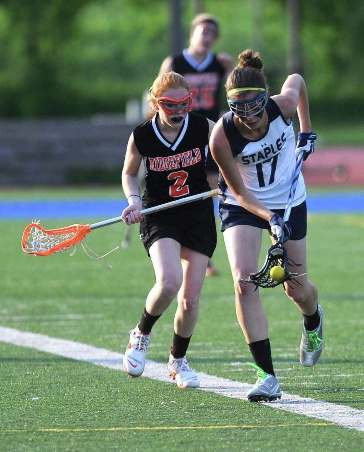 Staples' Elizabeth Driscoll carries the ball as Ridgefield's Casey Briody defends during Friday's game at Staples High School on May 20, 2011.