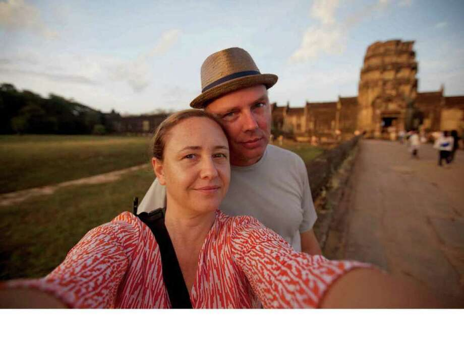 Photographer Carolyn Taylor takes a photo of herself and her husband, Chris, at Angkor Wat Temple in Cambodia. Taylor, a cancer survivor, won a grant to travel the world documenting cancer patients in developing countries. Photo: Contributed Photo / New Canaan News