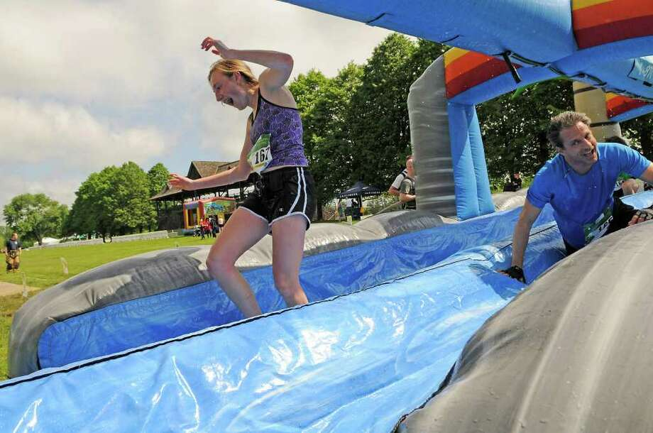 Danielli Scarfi and her dad Frank, both of Danbury, make their way through the slide as teams compete in the Leukemia & Lymphoma Society Pineapple Classic 5K at the Greenwich Polo Club in Greenwich on Saturday, May 21, 2011. Photo: Shelley Cryan / Greenwich Time