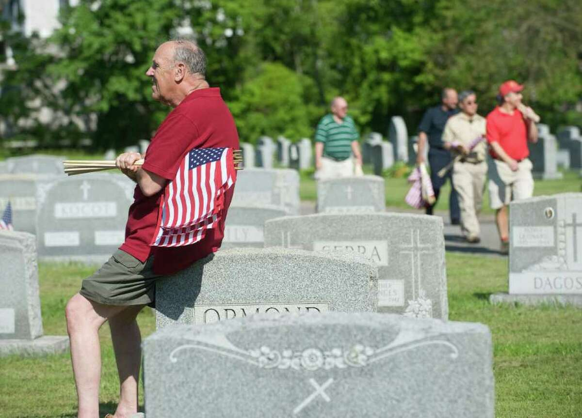 Bruce Vukson volunteers with the Veterans of Foreign Wars Post 9617-Springdale and other organizations as they place American flags on veterans graves at St. John's Cemetery in honor of Memorial Day in Stamford, Conn. on Saturday May 21, 2011.