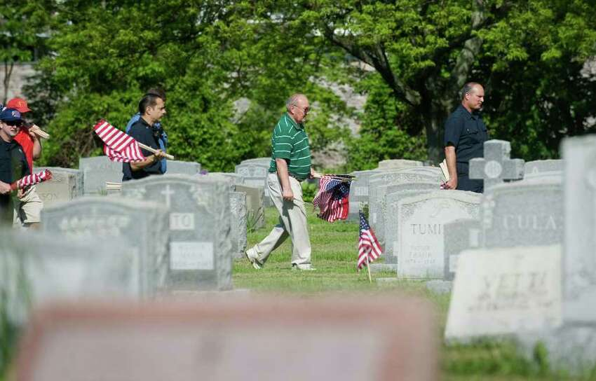 Veterans of Foreign Wars Post 9617-Springdale and other volunteers place American flags veterans graves at St. John's Cemetery in honor of Memorial Day in Stamford, Conn. on Saturday May 21, 2011.