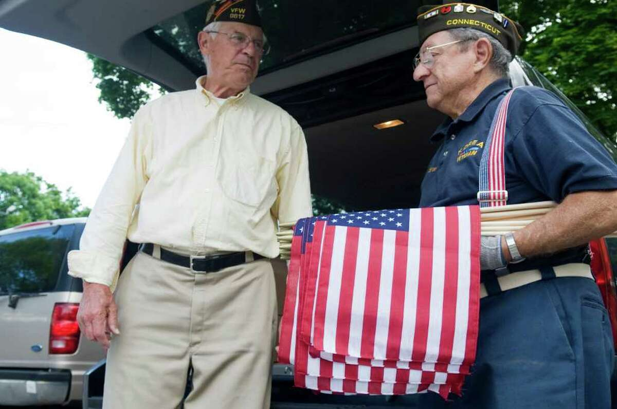 Fred Drenckhahn and Ralph Bocuzzo join other members of the Veterans of Foreign Wars Post 9617-Springdale as they place American flags on veterans graves at St. John's Cemetery in honor of Memorial Day in Stamford, Conn. on Saturday May 21, 2011.