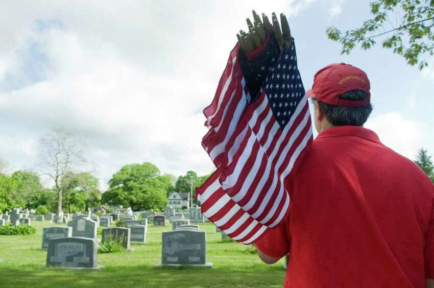 Members of the Veterans of Foreign Wars Post 9617-Springdale and other volunteers place American flags on veterans graves at St. John's Cemetery in honor of Memorial Day in Stamford, Conn. on Saturday May 21, 2011.