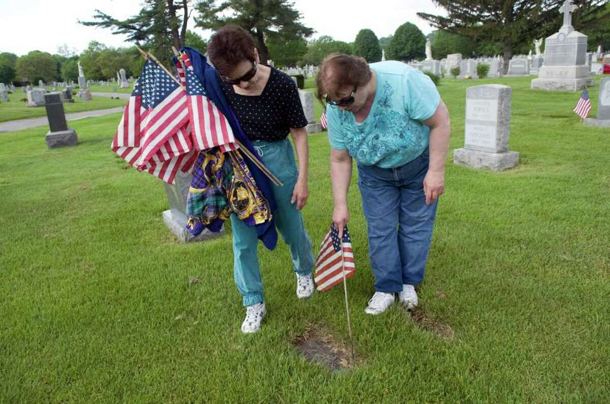 Suzanne LaBella and her sister Patti LaBella volunteer with member of the Veterans of Foreign Wars Post 9617-Springdale and other organizations as they place American flags on veterans graves at St. John's Cemetery in honor of Memorial Day in Stamford, Conn. on Saturday May 21, 2011.
