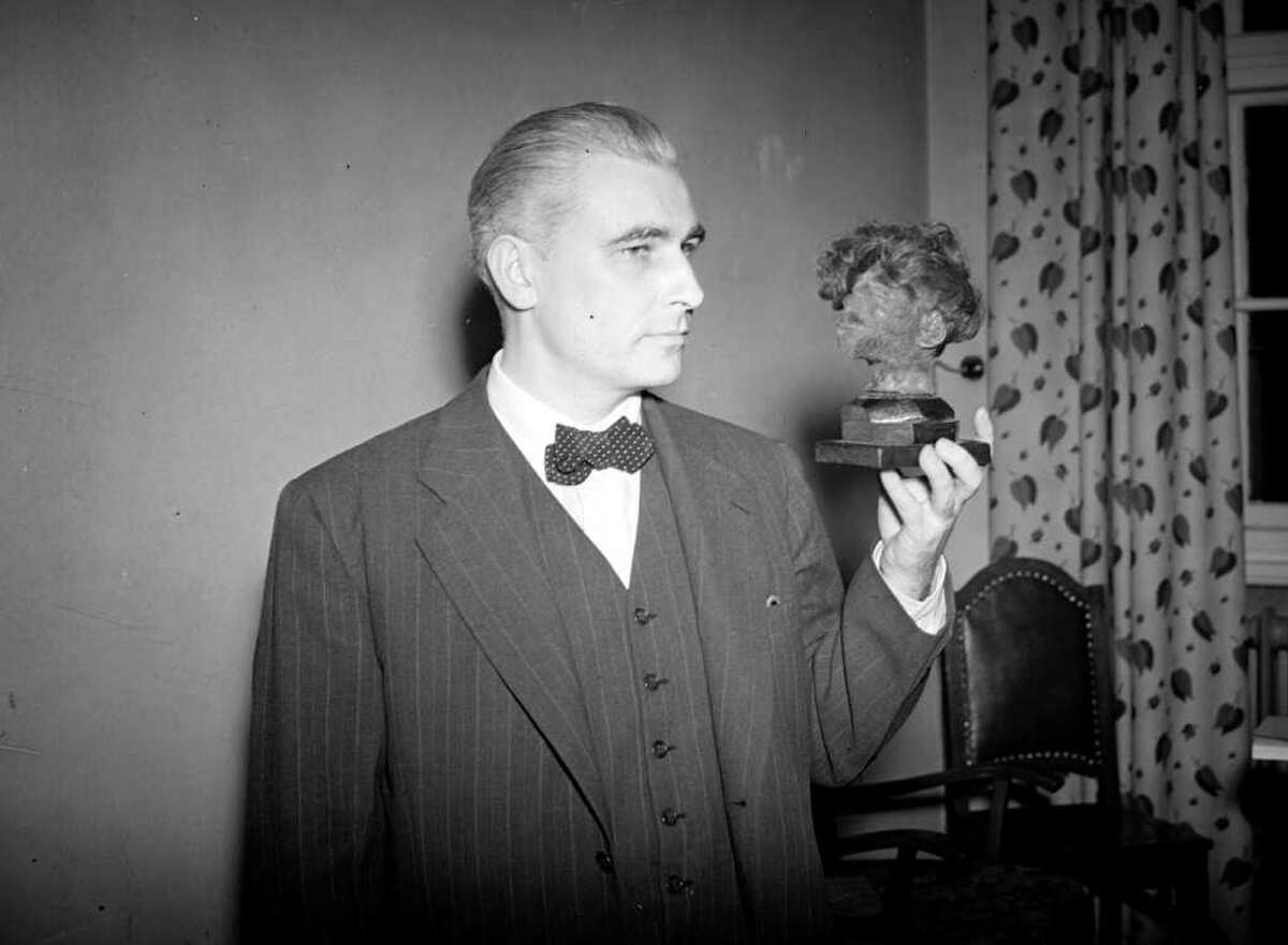 In this Dec. 17, 1945, photo, American prosecutor Thomas Dodd holds the shrunken head of a prisoner of war who died in the concentration camp at Belsen. (Photo by Allen/Express/Getty Images)