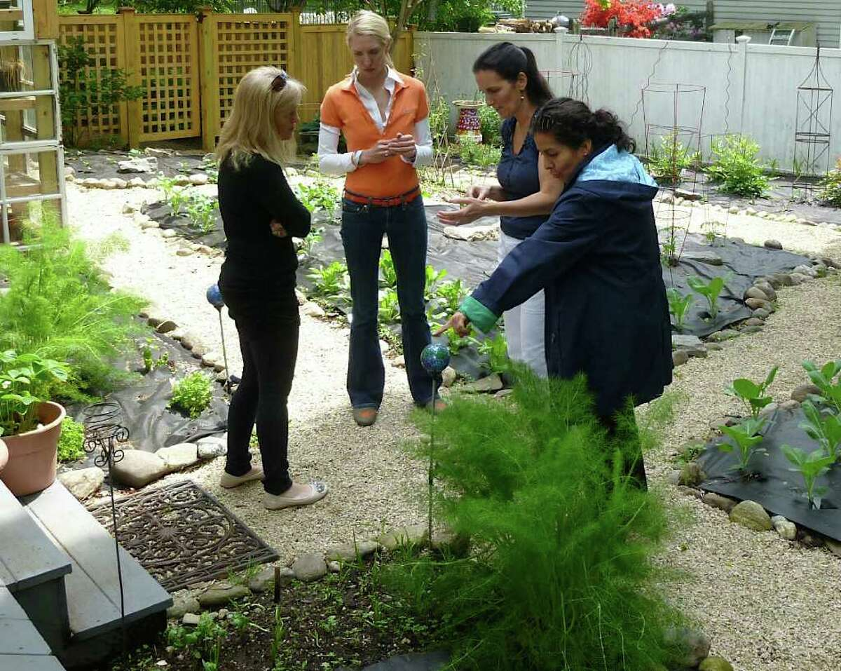 """Heather Carey, second from right, leads participants in her """"Kitchen Garden Workshop"""" on a tour of her home-based vegetable and herb garden."""