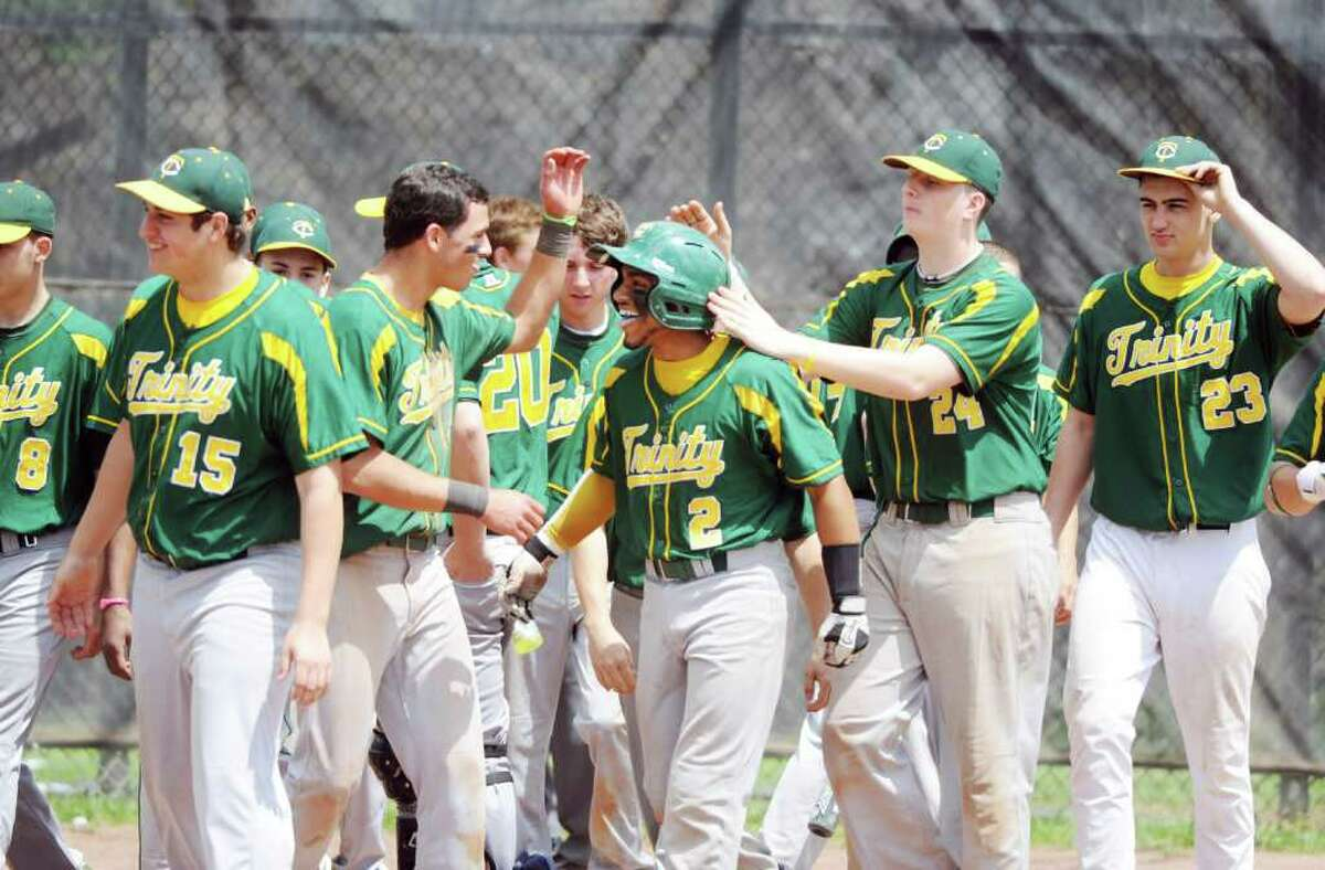 Trinity Catholic's Sammy Dominguez is congratulated by his teammates after a hitting a home run against Stamford High in baseball action in Stamford, Conn. on Saturday May 21, 2011. Trinity won the city title game 6-0.