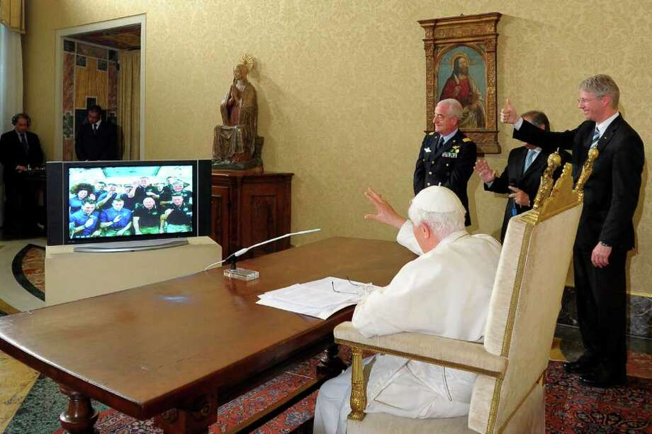 In this photo released by Vatican newspaper L'Osservatore Romano Pope Benedict XVI talks with astronauts, at the Vatican, Saturday, May 21, 2011. The 12 astronauts circling the Earth have received a call from Pope Benedict XVI, the first-ever papal call to space. The pope addressed the shuttle and station crews from the Vatican. Two Italians are on board: Endeavour astronaut Roberto Vittori and International Space Station resident Paolo Nespoli. The pope said he admired the astronauts' courage, discipline and commitment. (AP Photo/L'Osservatore Romano)  EDITORIAL USE ONLY Photo: L'Osservatore Romano / AP