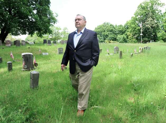 Ossining Historical Society President Norman MacDonald walks in Sparta Cemetery in Ossining, N.Y., Thursday afternoon, May 19, 2011.  MacDonald is part of an effort to solve the mystery of the identity of The Leather Man, a wanderer who died in 1889 and is thought to be buried in the cemetery. Photo: Bob Luckey / Greenwich Time