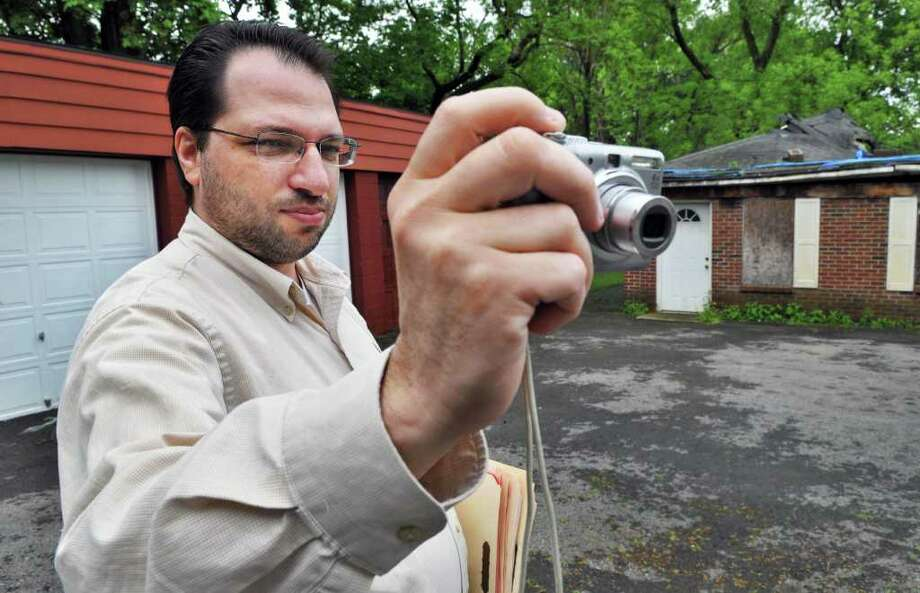 Real estate appraiser David Fontana photographs a multi-unit dwelling in Schenectady Friday morning May 20, 2011.   (John Carl D'Annibale / Times Union) Photo: John Carl D'Annibale / 00013220A