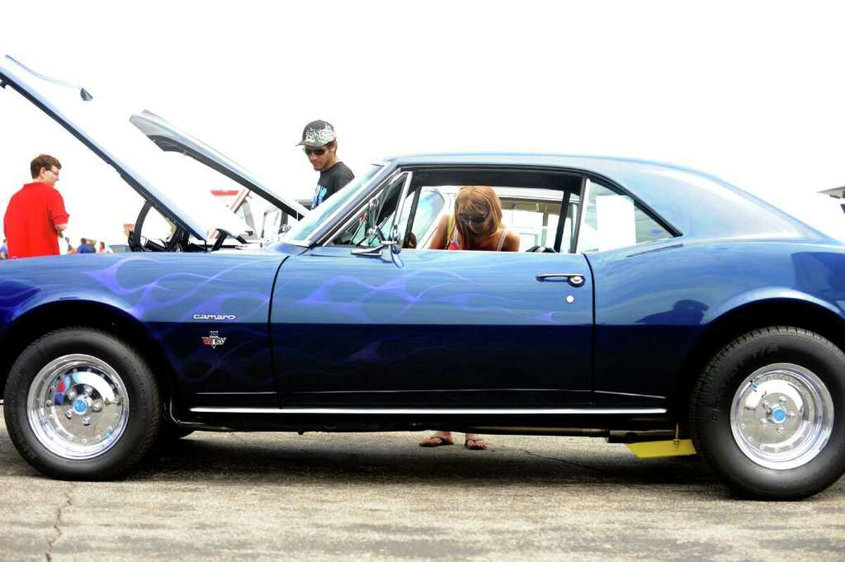 Rachel Howard, of Trumbull, peers into a 1969 Camero at the Wings and Wheels 2011; British Invasion show Saturday, May 21, 2011 at Igor I. Sikorsky Memorial Airport in Stratford, Conn.